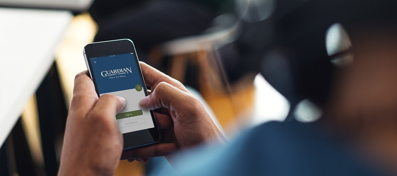 Man holds a phone in his hands while looking at the Guardian Credit Union Mobile app