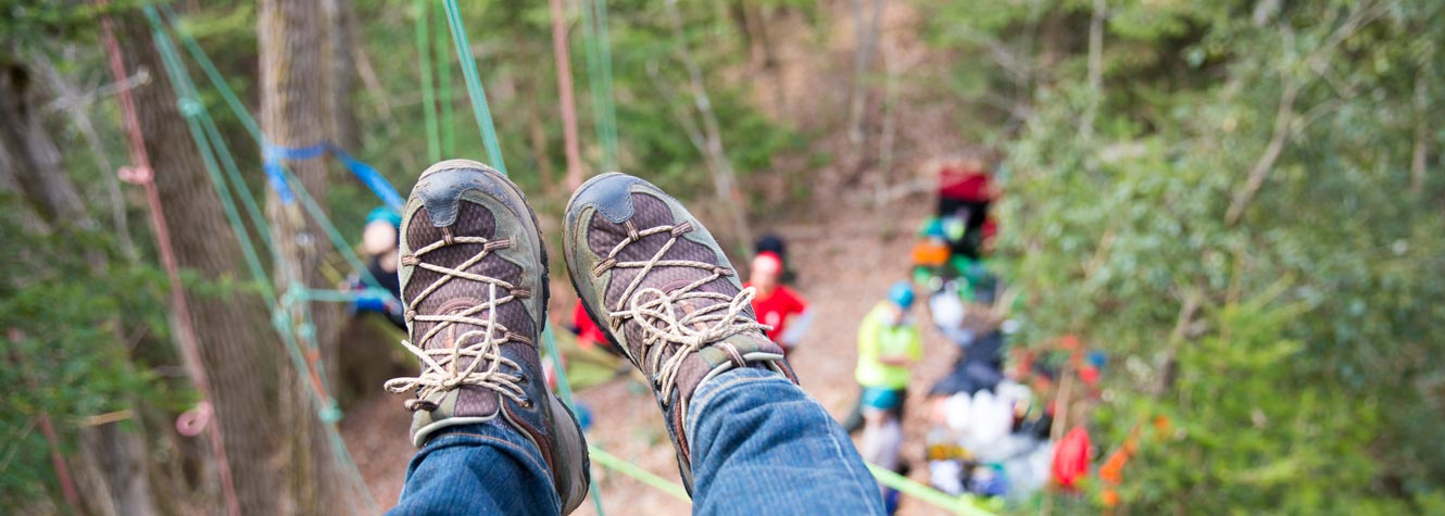 first person view of a person looking at their shoes as they slide down a zipline in the trees